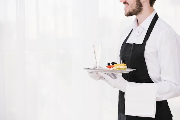 Bearded waiter holding tray with copy space