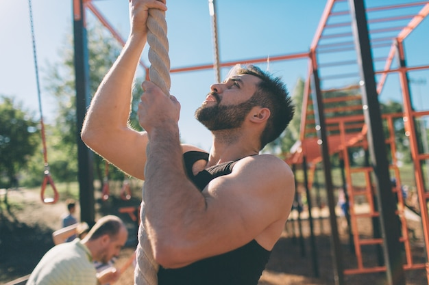 Bearded with black hair man climbing thick rope during fitness exercises in cross-fit training with. strong muscular hands.