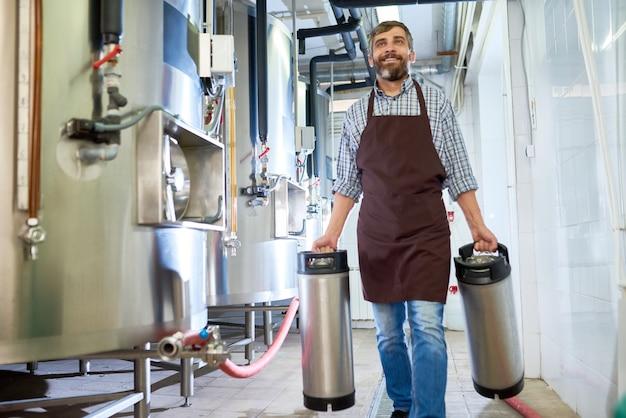 Bearded worker carrying beer kegs