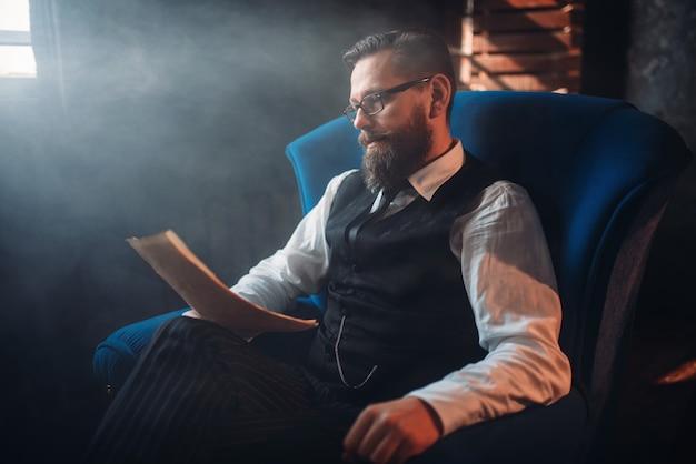 Bearded writer in glasses reads handwritten text