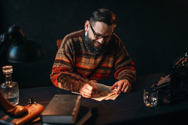 Bearded writer in glasses writes with a feather