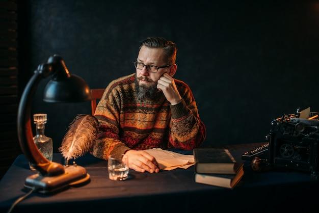 Бородатый писатель в очках сидит за столом