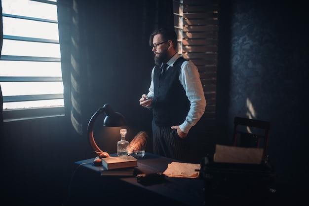 Бородатый писатель в очках курит сигарету
