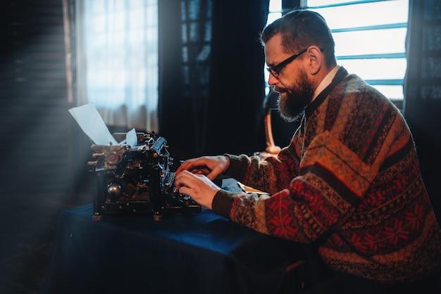 Бородатый писатель в очках печатает на пишущей машинке
