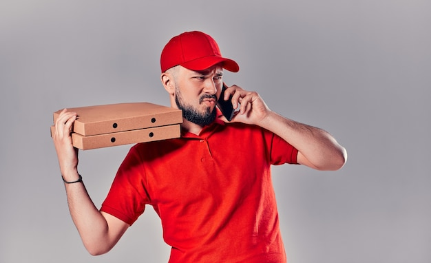 Бородатый молодой сердитый рассерженный курьер в красной футболке и кепке с коробками для пиццы и смартфоном, изолированным на сером фоне. быстрая доставка на дом.