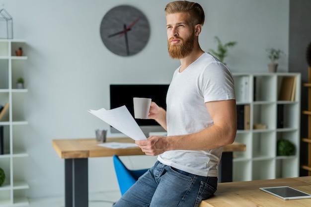 現代のオフィスで働くひげを生やした青年実業家。白いtシャツを着て、文書にメモをとる男。