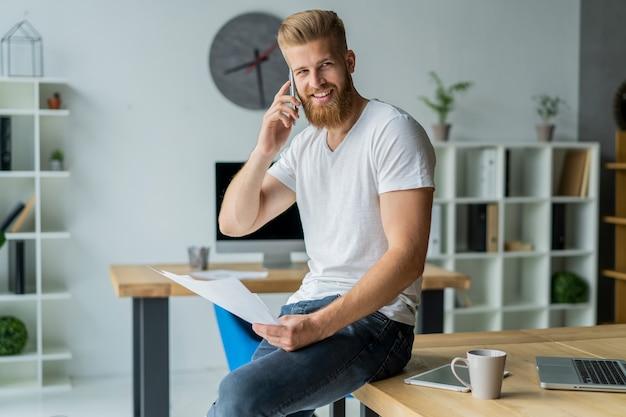현대 사무실에서 일하고 수염 된 젊은 사업가. 흰색 티셔츠를 입고 문서에 메모를 만드는 남자.