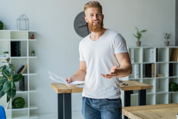 Бородатый молодой бизнесмен работает в современном офисе. человек в белой футболке и делает заметки на документах.