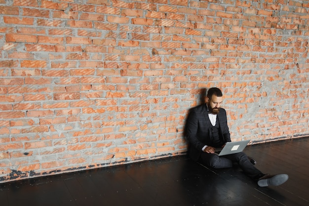 노트북을 들고 바닥에 앉아 현대 로프트 사무실에서 작업 수염 된 젊은 사업가.
