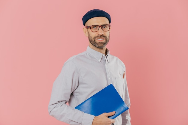 Bearded young caucasian man student holds textbook, prepares for final examination, wears glasses