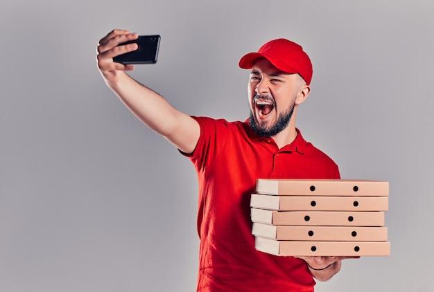 빨간 티셔츠를 입은 수염난 배달원과 피자 상자가 든 모자를 쓴 배달원은 회색 배경에 격리된 스마트폰으로 셀카를 찍는다. 빠른 집 배달.