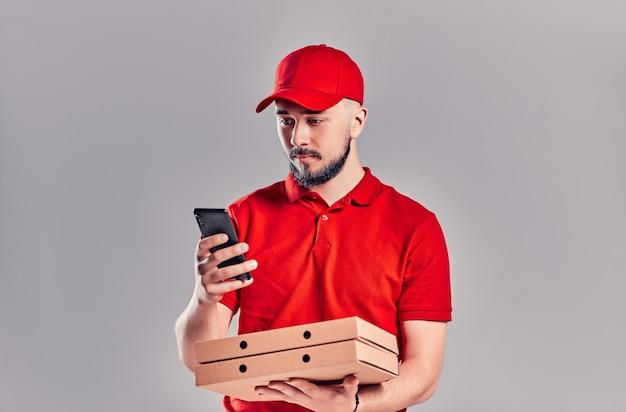 빨간 티셔츠와 모자를 쓴 수염난 배달원, 피자 상자와 스마트폰이 회색 배경에 격리되어 있습니다. 빠른 집 배달.