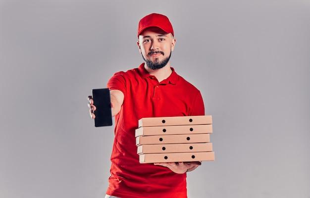 빨간 티셔츠에 피자 상자가 달린 모자를 쓴 수염난 배달원은 회색 배경에 격리된 빈 스마트폰 화면을 보여줍니다. 빠른 집 배달.