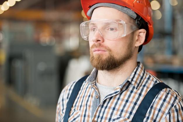 ワークショップに立っている近代的な工場や産業プラントのひげを生やした若いエンジニア