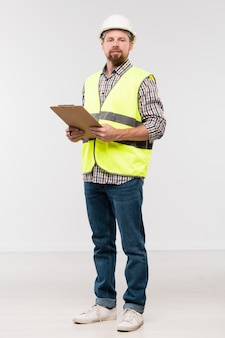 Bearded young engineer with clipboard standing in front of camera in isolation and looking at you