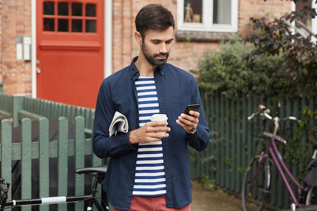Bearded young guy reads information on phone