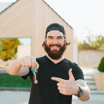 Bearded  young male smiling, holding some keys and with his left hand pointing at his house in the back