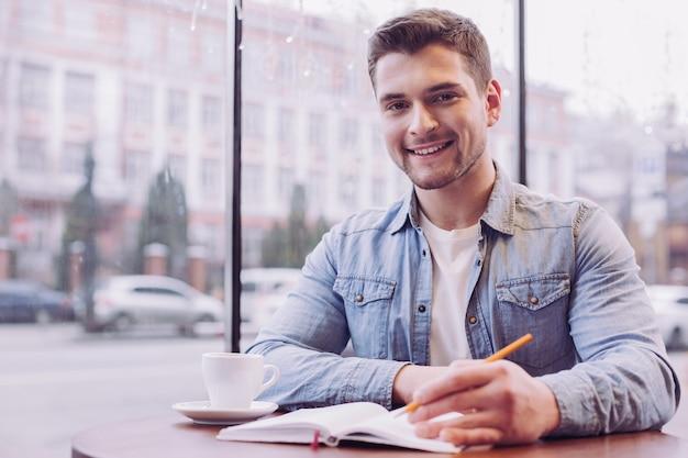 Бородатый молодой студент-мужчина записывает информацию, улыбаясь и глядя прямо