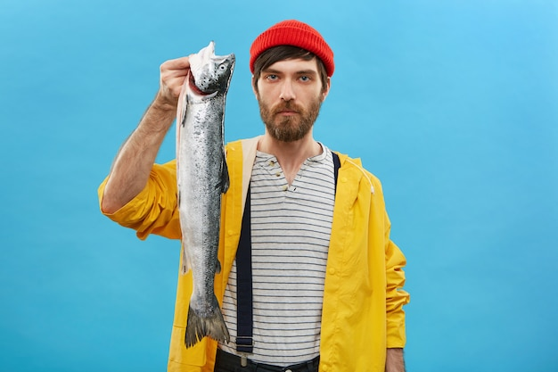 Bearded young man angling big fish in pond, posing with it over blue wall having serious expression. successful fisherman holding long big salmon in hands, demonstrating his huge catch