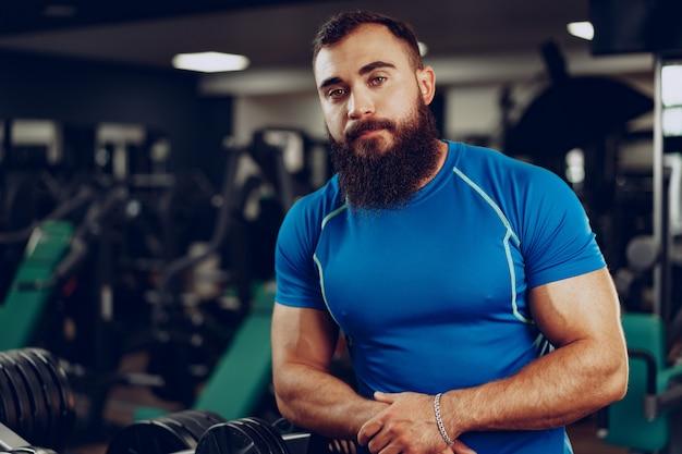 Бородатый молодой человек культурист в синей футболке, стоя в тренажерном зале