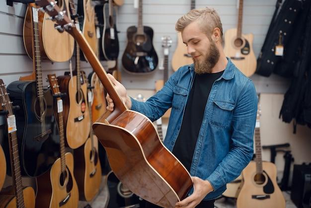 Бородатый молодой человек выбирает акустическую гитару в музыкальном магазине.