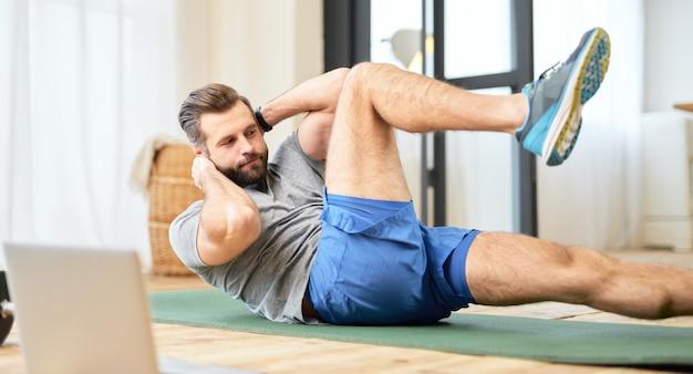 Бородатый молодой человек делает упражнения на пресс дома