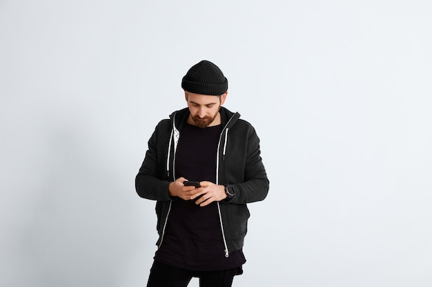 Il giovane barbuto vestito in abiti casual tutti neri e blu scuro guarda nel suo smartphone isolato su bianco