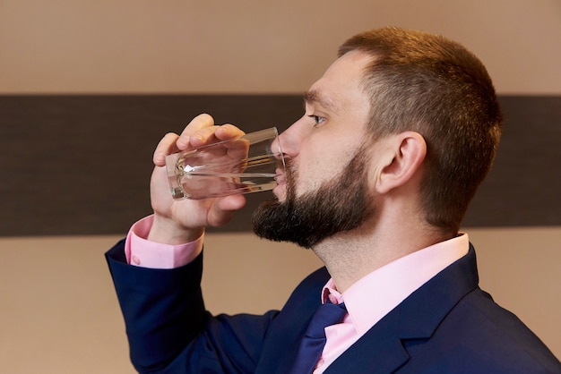 A bearded young man drinking water from a glass.