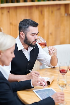 Bearded young man in formalwear smelling various sorts of wine while making notes in notepad by workplace
