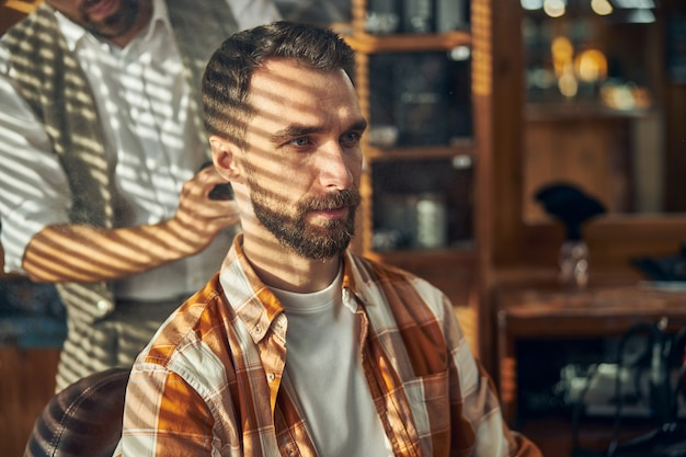 A bearded young man having an appointment at a stylish barbershop
