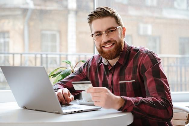 デビットカードを保持しているひげを生やした若い男。