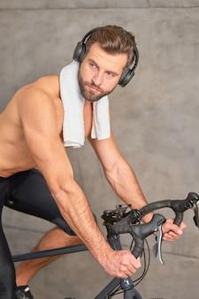 Бородатый молодой человек в наушниках на канцелярском велосипеде