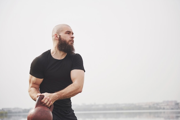 The bearded young man is engaged in outdoor sports