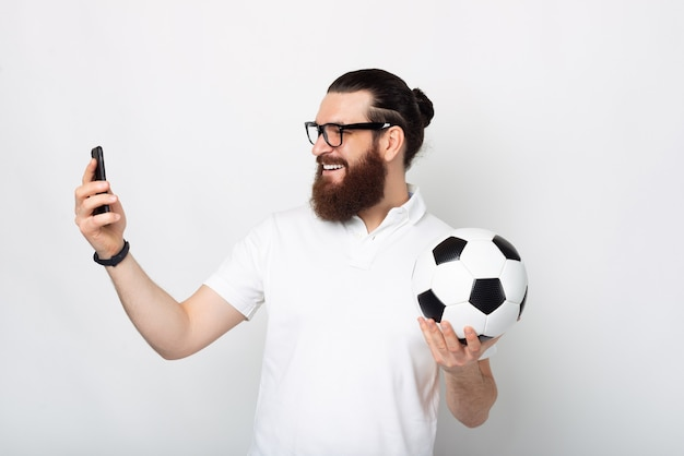 Бородатый молодой человек разговаривает с кем-то по телефону и улыбается, держит футбольный мяч возле белой стены