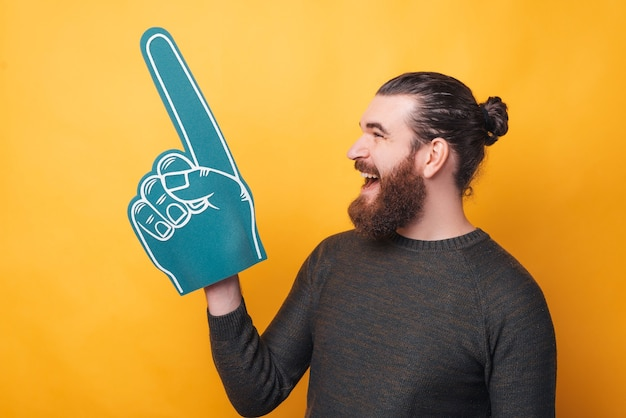Bearded young man is holding a fan glove and screaming is looking away