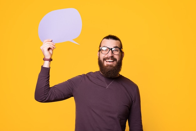 Bearded young man is holding a speech bubble and smiling
