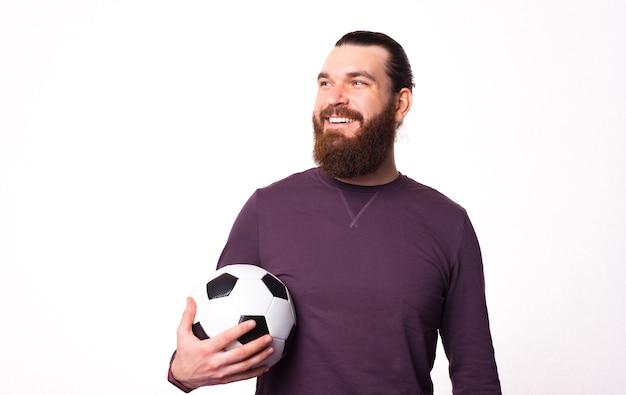 Бородатый молодой человек смотрит в сторону, улыбаясь и держит футбольный мяч