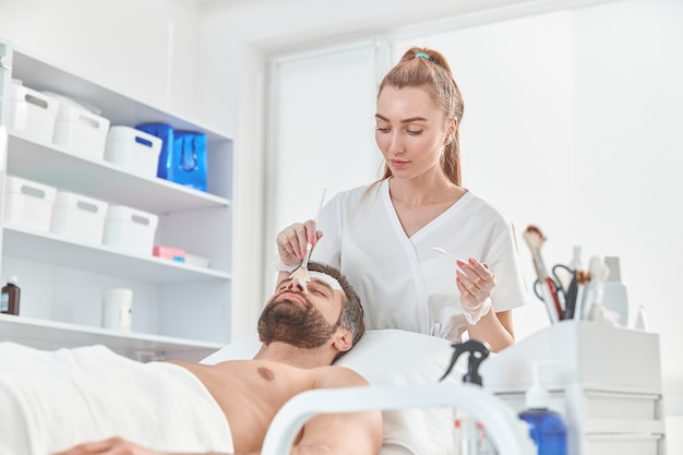 Bearded young man is relaxing while cosmetologist is spreading white clay on his face