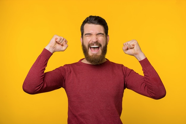 Bearded young man is screaming of joy with both of his hands up near yellow background.