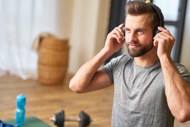 Бородатый молодой человек слушает музыку дома