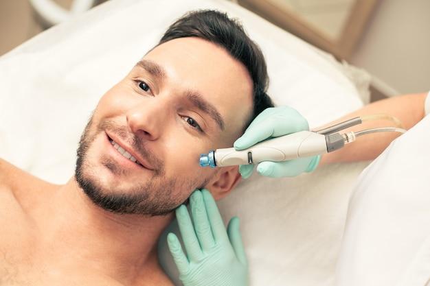 Бородатый молодой человек выглядит радостным и улыбается, держа современное устройство, касаясь его щеки во время процедуры увлажнения