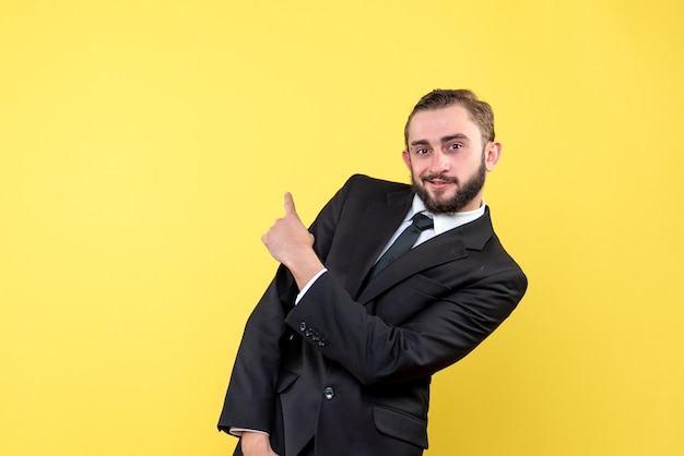黄色の上に何かを指しているひげを生やした若い男