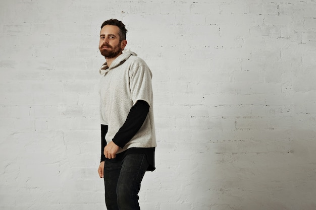 A bearded young man presenting a soft cotton plain gray sweatshirt with black jeans isolated on white