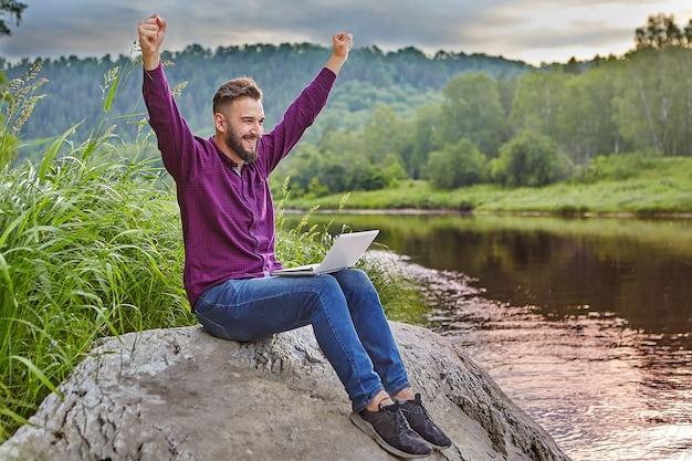 あごひげを生やした若い男は、ラップトップを膝に抱えて川の近くの岩の上に座って、手を上に上げて喜んでいます。