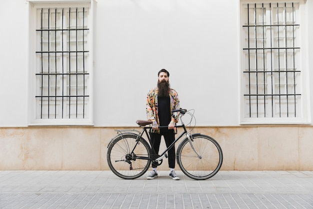 Bearded young man standing with bicycle against wall