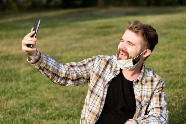 Selfieを取ってひげを生やした若い男