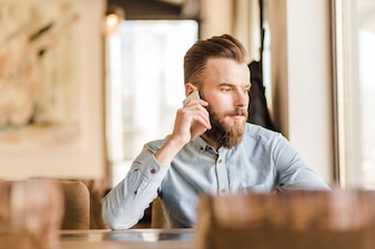 Bearded young man talking on cellphone in restaurant