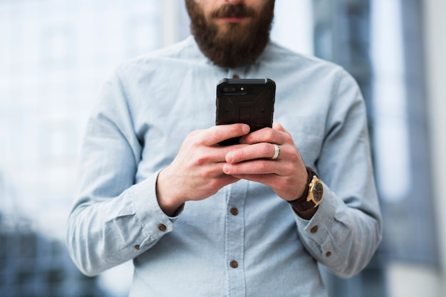Bearded young man text messaging on mobile phone