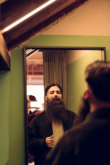 Bearded young man trying jacket in front of mirror
