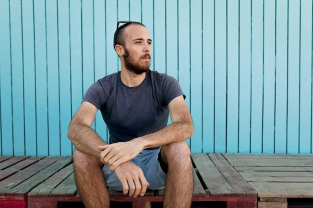 Бородатый молодой человек в солнцезащитных очках над головой уверенно смотрит в сторону на пляж исла канела на фоне синей деревянной стены.